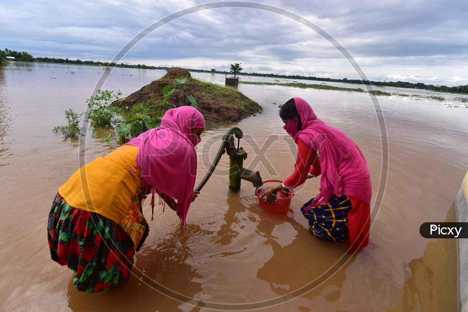 Two girls fetch water from a partially submerged hand pump at Madhab Para village in Nagaon, Assam on July 22, 2020
