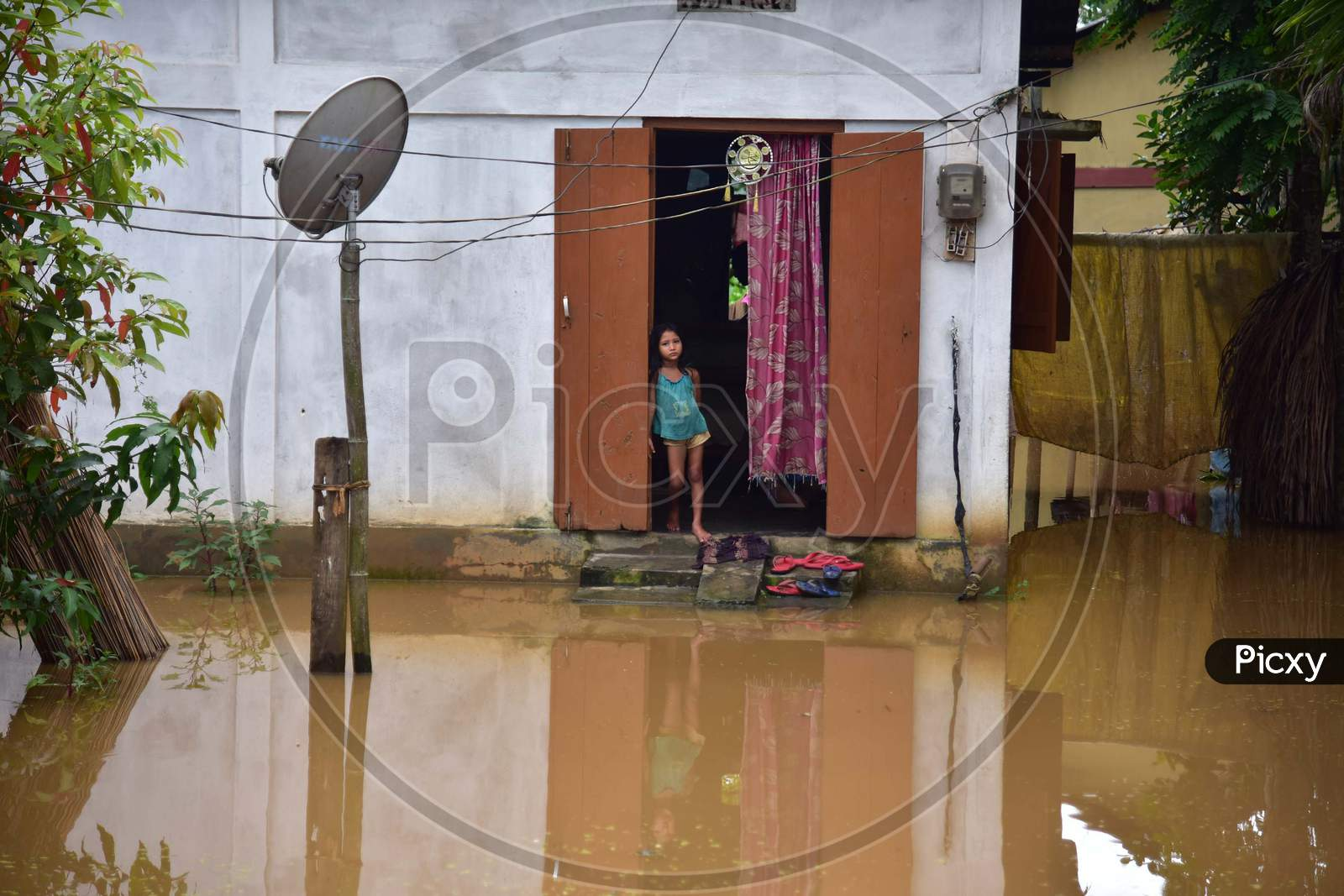 A girl stands near the door of her partially submerged house in a flood-affected village in Nagaon, Assam on July 22, 2020
