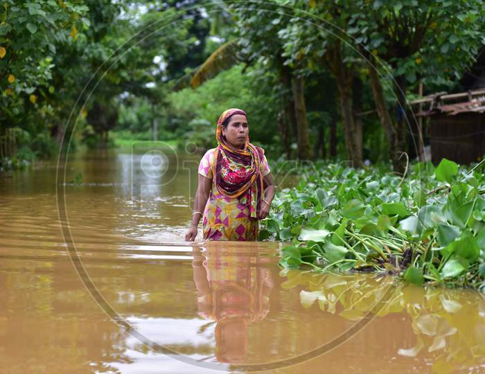 A woman wades through floodwaters in a flood-affected village in Nagaon, Assam on July 22, 2020