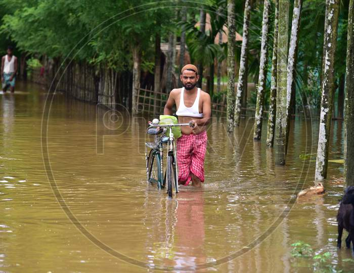 A man wades his way through flooded waters in a flood-affected area in Nagaon, Assam on July 22, 2020