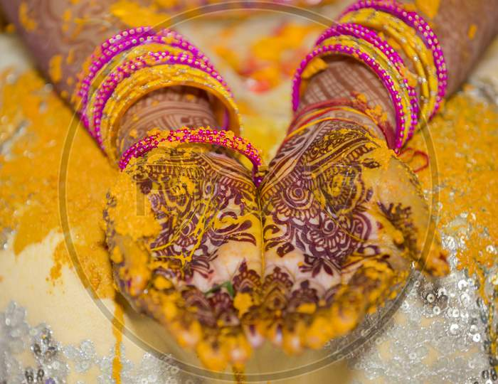 bride's hand painted with fresh turmeric paste.
