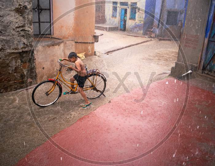 A boy riding bicycle and having fun in rain during monsoon in Bharatpur