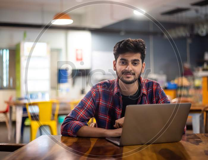 Smiling young Indian man working on a laptop in office