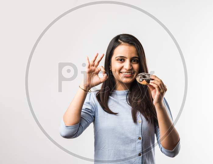 Indian Girl Eating Chocolate Donut, Isolated Over White Background