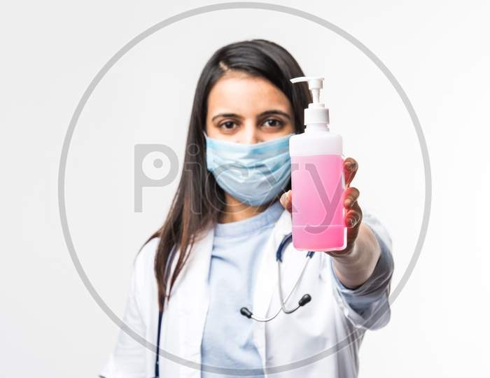 Indian Female Doctor In Uniform And Face Mask Using Sanitizer Or Disinfectant Spray