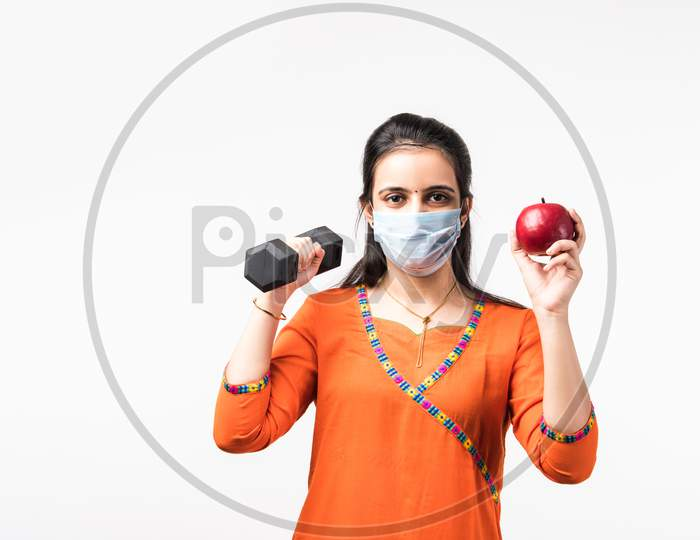Indian Pretty Girl Exercising With Dumbbell And Showing Fresh Apple While Wearing Medical Face Mask