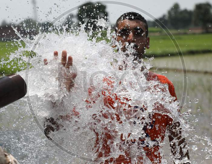 A young man enjoys the cool splash from a tube well on a hot summer day during Unlock 2.0 in Jammu on July 03, 2020.