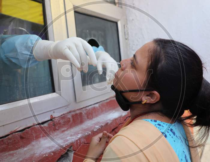 Health worker collects a swab sample from a patient at a Government Hospital for Covid-19 test in Jammu on July 03, 2020