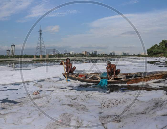 Indian Fishermen Use A Fishing Net In The Polluted Waters Of The Yamuna River On July 30, 2020 In New Delhi, India.