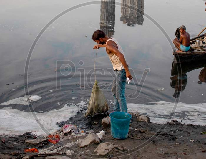 Indian Fishermen Use A Fishing Net In The Polluted Water Of The Yamuna River On July 30, 2020 In New Delhi, India.