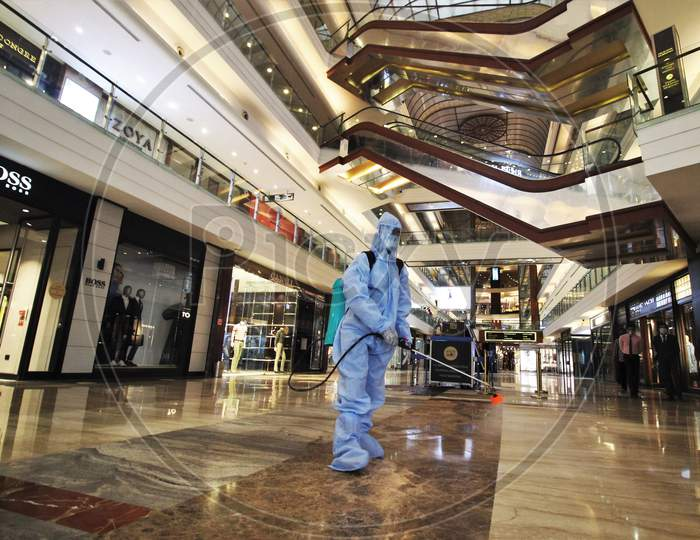 A man in personal protective equipment (PPE) sprays disinfectant to sanitize a mall before they reopen in Mumbai, India on July 30, 2020.