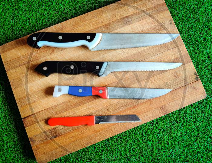 Four Colored Different Sizes Of Knives Kept On Chopping Board.