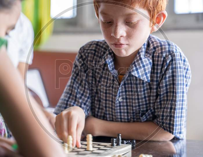 Serious Chess Player Kid Thinking And Moving Coin At Home - Concept Of Kid Concentration Of Game During Early Development, Home Educational Games For Children