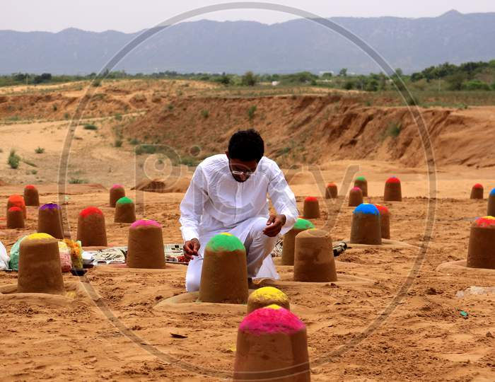 Indian sand artist Ajay Rawat creates 108 shivalings on the first Monday of 'Sawan'month in Pushkar, Rajasthan on July 06, 2020.