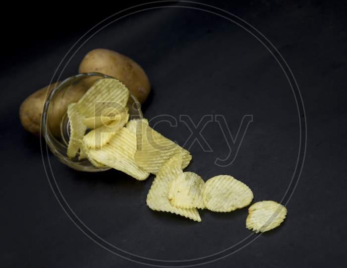 Crispy potato chips in bowl on dark table