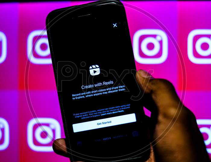Instagram new update Instagram Reels on a Mobile Screen with a finger about to touch and Instagram logo in the background