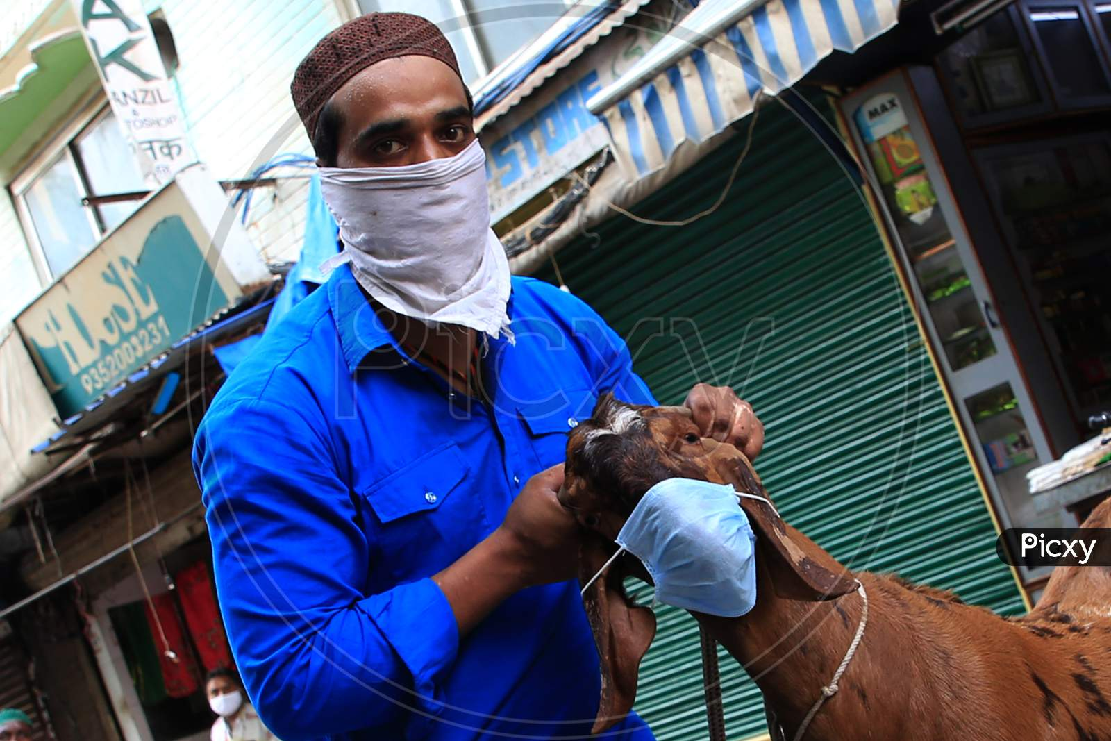 A Man Holds A Face Mask Against The Face Of A Goat During  Eid Al-Adha, The Feast Of Sacrifice Outside The Shrine Of Sufi Saint Khwaja Moinuddin Chishti In Ajmer, On August 1, 2020.