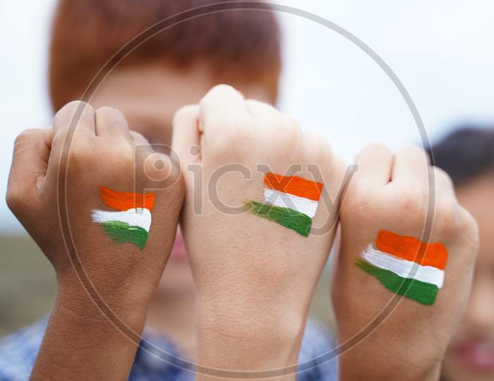 Kids Fist Hands Painted With Indian Falg During Independence Day Or Republic Day Celebration - Concept Showing Of Solidarity, Raised Fist Of A Protesters Or Patriotism