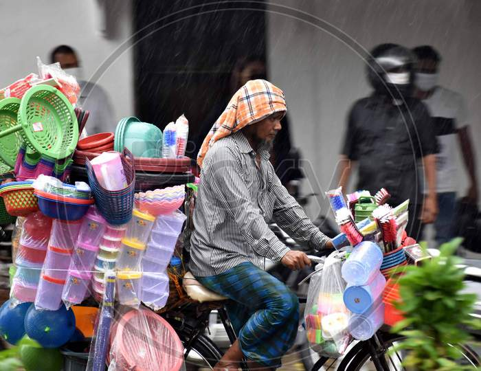 A vendor cycles on the road during heavy rains in Prayagraj, August 12, 2020.