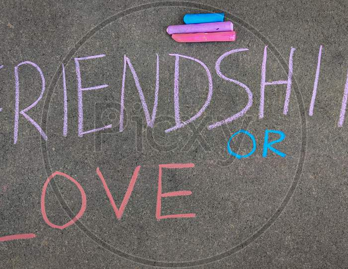 The Inscription Text On The Grey Board, Friendship Or Love. Using Color Chalk Pieces.