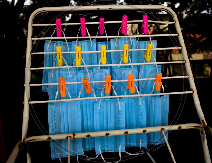 Corona Virus Pandemic Masks Being Hanged On A Cloth Rod After Cleaning. Reusable Blue Colored Face Masks