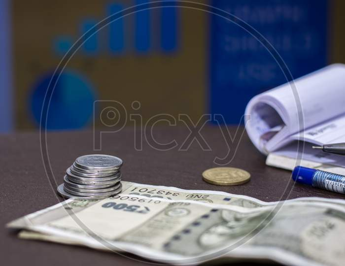 A Stack Of Indian Coins And Few Notes With Business Graph In Background