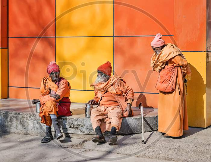 Sadhus in orange and yellow holy colours sitting in the winter sun outside a holy Hindu temple in Haridwar, northern India