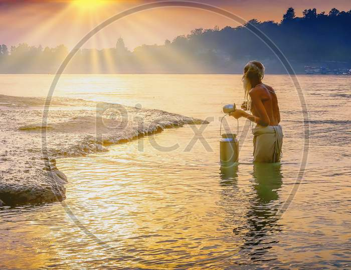 A pilgrim bathing in the holy waters of the Ganges at Rishikesh a city in India's northern state of Uttarakhand, in the Himalayan foothills beside the Ganges River.