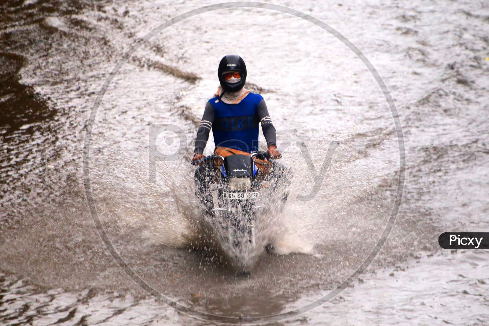 A man drives through a flooded road during heavy rains in Ajmer, On August 1, 2020.