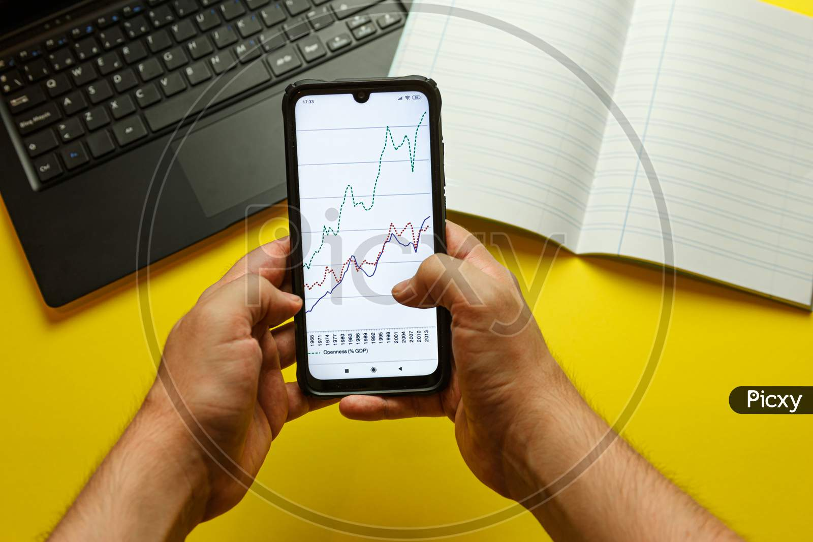 Point Of View Of Two Young Hands Grabbing A Phone With An Economical Graphic In It