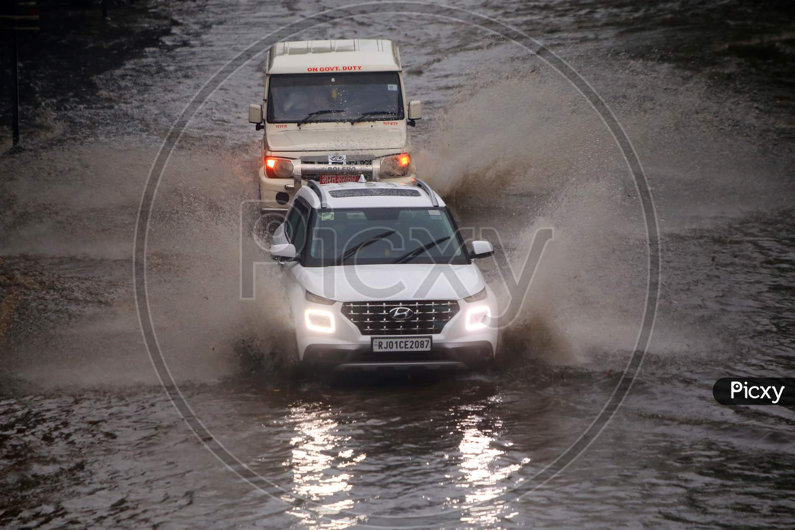 People drive through a flooded road during heavy rains in Ajmer, On August 1, 2020.