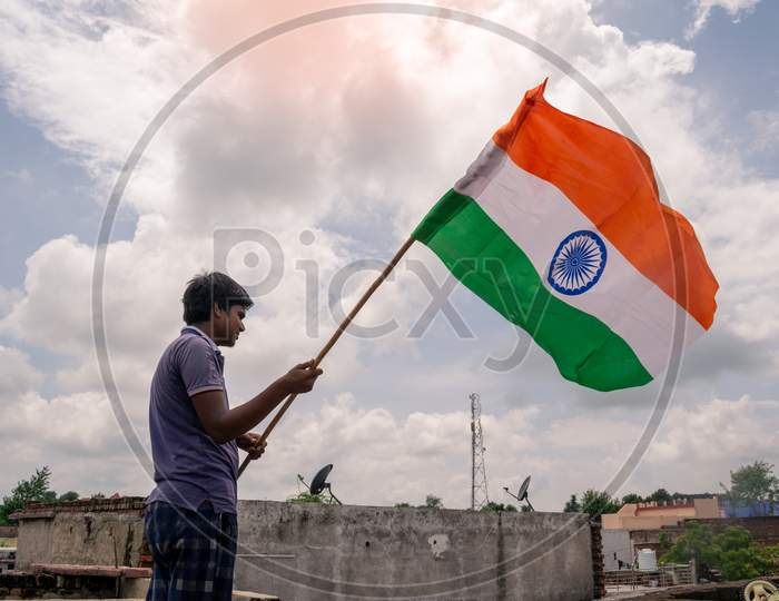 A boy holds indian flag or tricolour flag to celebrate independence day on 15 august 2020