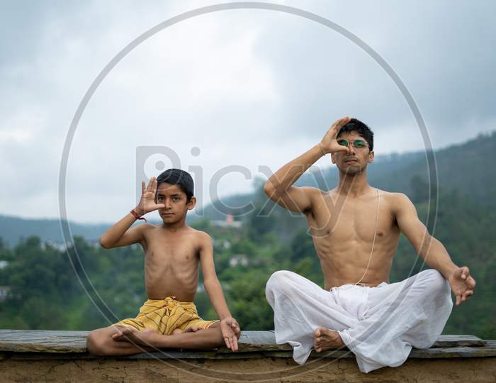 A Young Handsome Boy Doing Yoga With A Kid On The Roof Of A House Situated In The Middle Of Mountain Range. Yoga And Fitness.