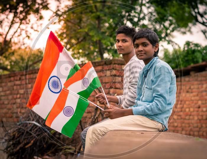 boys hold indian flags or tricolour flags on the independence day at a farm, 15 august 2020
