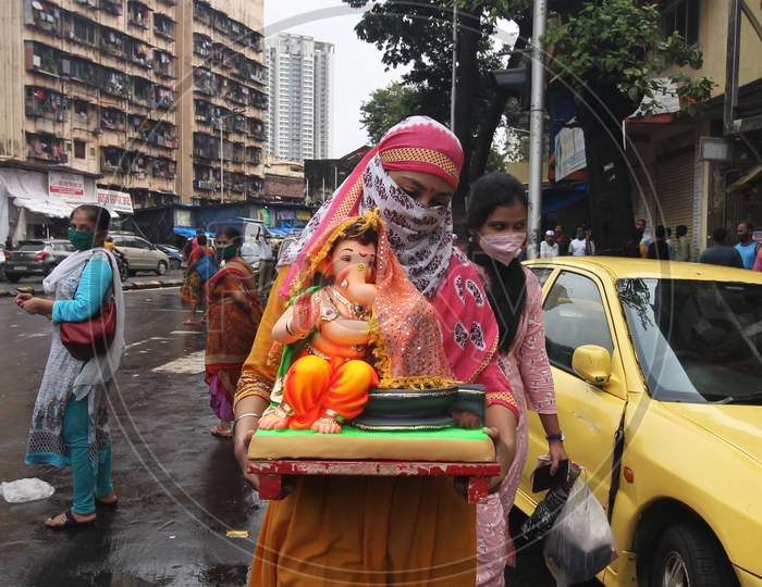 A devotee wearing a mask carries home an idol of elephant-headed Hindu god Ganesha for worship during Ganesh Chaturthi festival celebrations in Mumbai, India, on August 22, 2020.