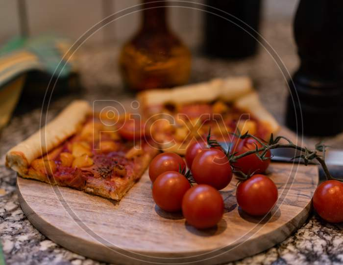 Pizza On A Cutting Board With Fresh Tomatos And Oil And Pepper Mill.