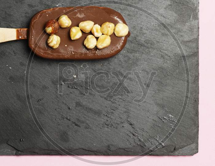 Chocolate Ice Cream With Organic Hazelnuts On Dark Slate Background. Flat Lay. Gastronomic Food