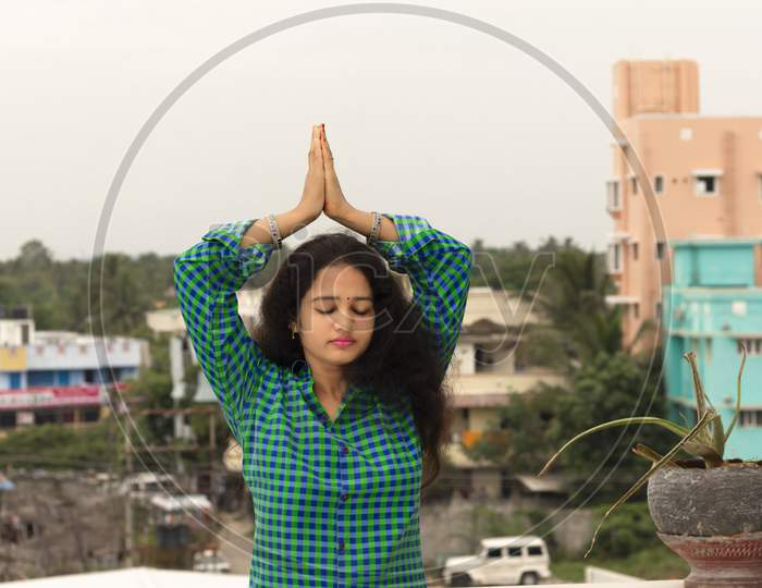 A Young Hindu Woman Standing In An Open Environment, Closing Her Eyes And Folding Her Hands Above The Head To The Sun God