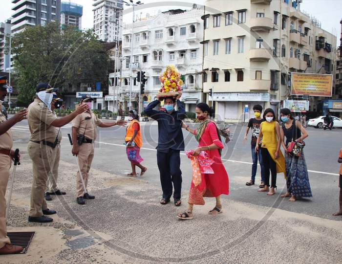 Police personnel are seen ensuring that only two family members with an idol enter for ganesh immersion at Girgoan Chowpatty, during the Ganesh Chaturthi festival in Mumbai, India on August 23, 2020.