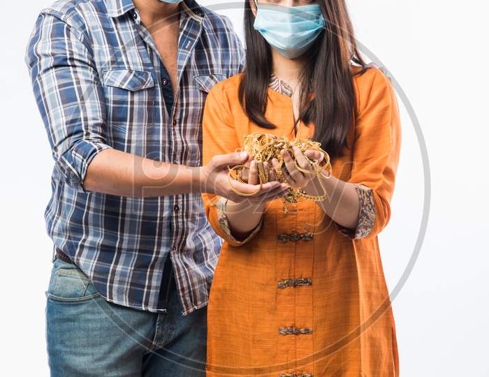 Indian Young Couple Wearing Face Mask And Holding Gold Jewelry Or Ornaments In Hand