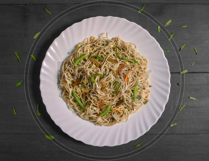 Vegetarian Schezwan Noodles Or Vegetable Hakka Noodles Or Chow Mein In White Plate At Wooden Background. Schezwan Noodles Is Indo-Chinese Cuisine Hot Dish With Udon Noodles, Vegetables And Chilli Sauce