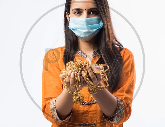 Indian woman holding gold ornaments or jewellery while wearing face mask