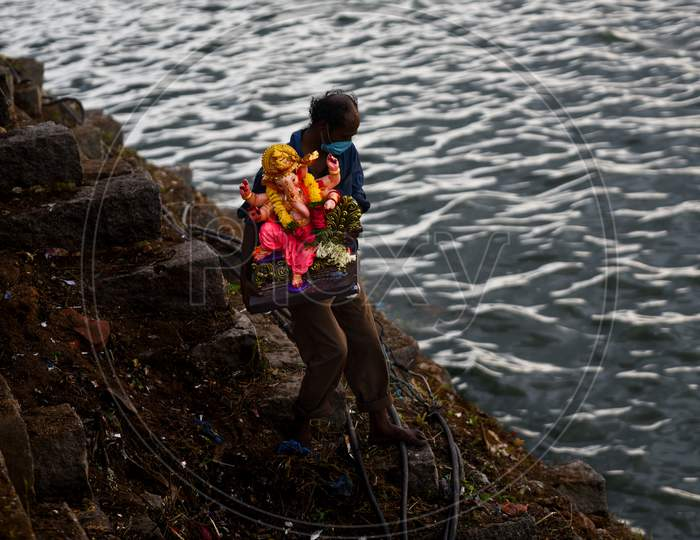 A GHMC worker with a facemask carries the idol of Hindu deity, Lord Ganesh to immerse in Hussain Sagar on August 25, 2020