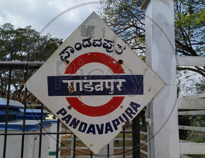 Location Name Board Of Pandavapura, In A Railway Station In A Diamond Shape With Red And Blue Color.