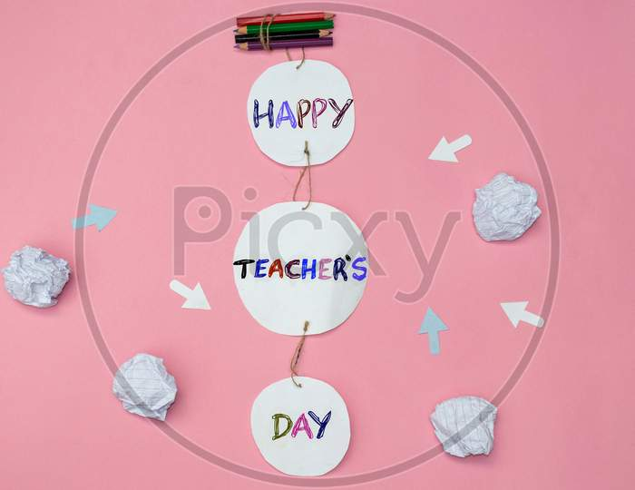 Happy Teacher's Day Creative Photo With Color Pencils And Crumpled Paper Balls On Pink Background, Perfect For Wallpaper