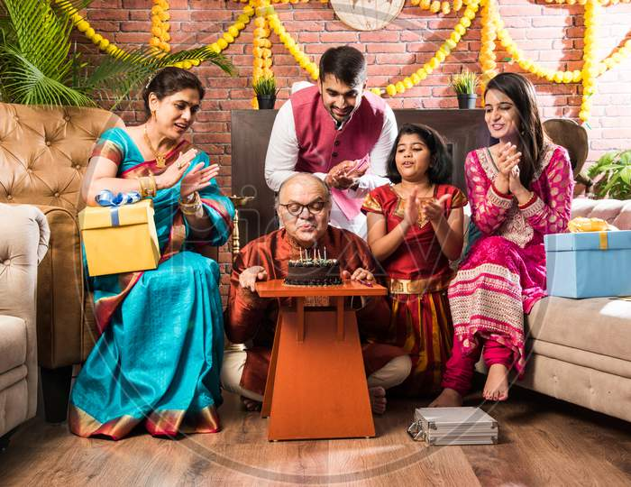Senior Indian Asian Man Celebrating Birthday With Wife, Son, Daughter In Law And Grand Daughter