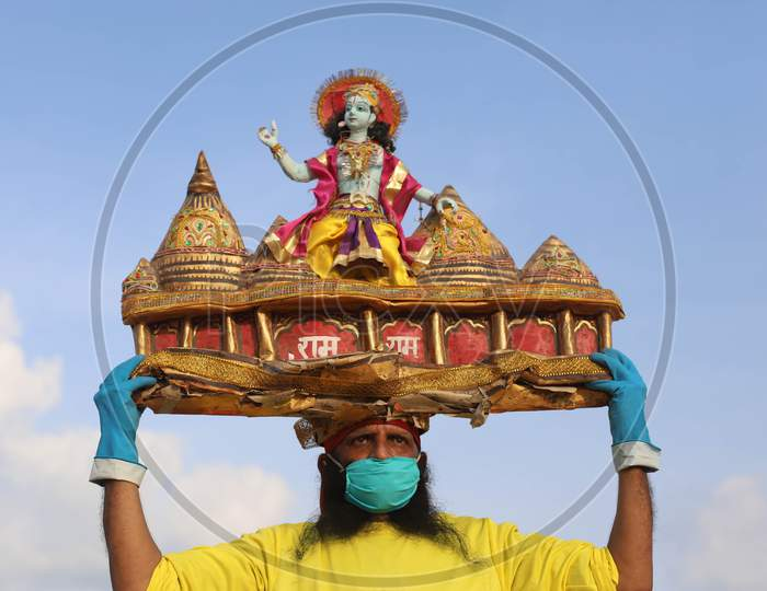 A man holds sculpture of Ram Temple, ahead of the foundation ceremony of Ram temple in Ayodhya, on the banks of River Ganga at Sangam, in Prayagraj, August 4, 2020.