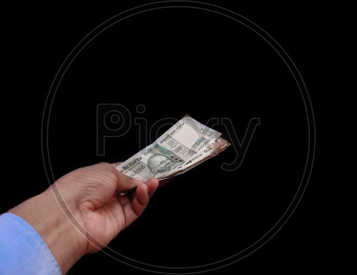 Banknote currency in hand of man , isolated on black background.