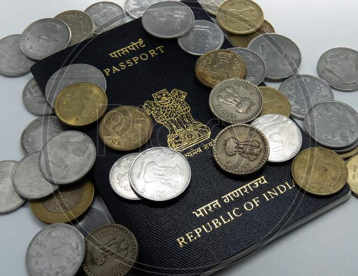 Image Of Indian Passport On White Desk With Rupee Coins.