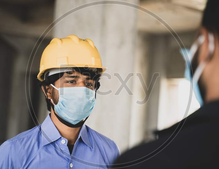 Two Construction Workers Or Engineers At Site Talking By Wearing Medical Face Mask While Maintaining Social Distance - Concept Of Business, Industry Reopen Or Covid-19 Safety Measures At Workplace.